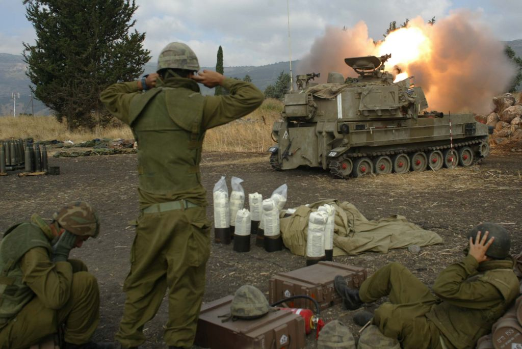 Israeli soldiers cover their ears as they fire artillery shells at southern Lebanon from outside Kiryat Shmona in northern Israel during the Second Lebanon War on July 22, 2006. (Pierre Terdjman/Flash90)