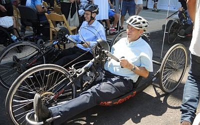 Tourism Minister Yariv Levin (left) and Tel Aviv Mayor Ron Huldai try out hand cycles on newly-adapted accessible bike paths at the dedication of the Accessible Cycling Complex on July 28, 2016. (Melanie Lidman/Times of Israel)