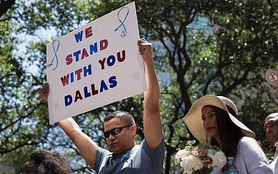 A man holds a sign during a vigil at Thanks-Giving Square in Dallas, Texas, on July 8, 2016, following the shootings during a peaceful protest on July 7 which left five police officers dead. (Laura Buckman/AFP/Getty Images/JTA)