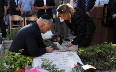Prime Minister Benjamin Netanyahu with his wife Sara at the grave of his late brother Yoni Netanyahu who was killed in the 1976 raid on Entebbe, on June 28, 2006. (Moshe Milner/GPO/Flash 90)