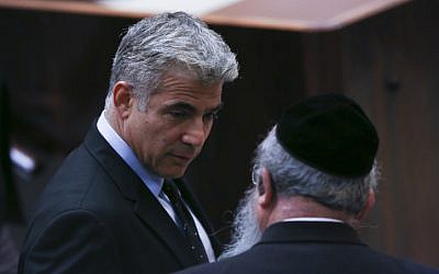 Yesh Atid leader Yair Lapid seen speaking with United Torah Judaism parliament member Menachem Eliezer Mozes on July 08, 2013. (Yonatan Sindel/FLASH90)