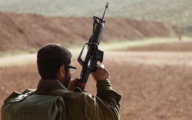 Illustrative: An IDF soldier holding a weapon. (Yaakov Naumi/Flash90)