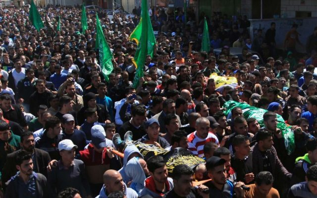 Palestinians carry two bodies during the funerals of Yazan Basim, Mahmoud Abu Zena and Hamza Abu Al-Haija, at Jenin Refugee Camp in the West Bank on March 22, 2014. (Issam Rimawi/Flash90)