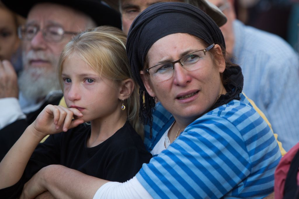 The mother and a younger sister of Hallel Yaffa Ariel mourning during her funeral ceremony in the Jewish settlement of Kiryat Arba, in the West Bank, on June 30, 2016. Earlier in the day, a 17-year-old Palestinian terrorist broke into their home and stabbed and killed 13-year-old Hallel in her bedroom. (Yonatan Sindel/Flash90)