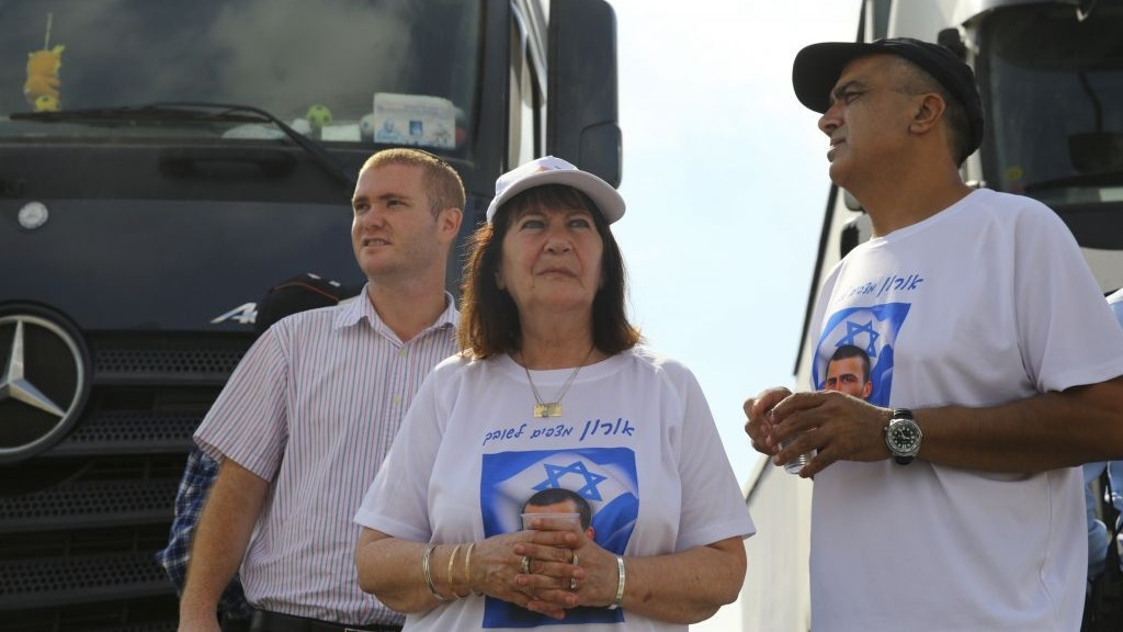 Parents of fallen IDF soldier Oron Shaul and friends block trucks heading to the Gaza Strip at the Erez Crossing in southern Israel, on July 3, 2016, after the cabinet voted to approve the reconciliation agreement with Turkey. (Flash90)
