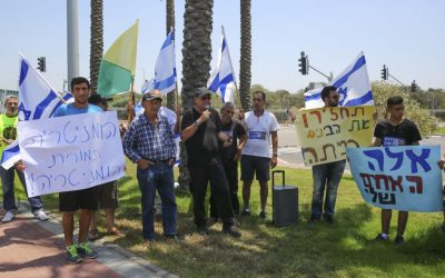 Friends and family of an Israeli soldier whose remains are being held by Hamas protest outside the Ashdod port in southern Israel on July 3, 2016, as the Lady Leyla, a Turkish ship carrying aid for Gaza, arrives (Flash90)