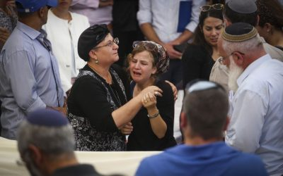 Friends and family mourn near the body of terror victim Rabbi Miki Mark during his funeral service at the Otniel yeshiva on July 3, 2016. (Hadas Parush/Flash90)