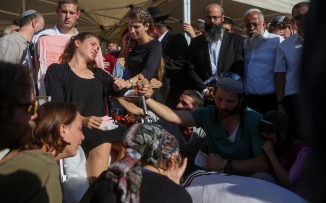Tehila Mark, wounded in a terror attack that killed her father, Miki Mark, attends his funeral along with other members of their family at the Har Hamenuhot cemetery in Jerusalem on Sunday, July 3, 2016 (Miriam Alster/Flash90)