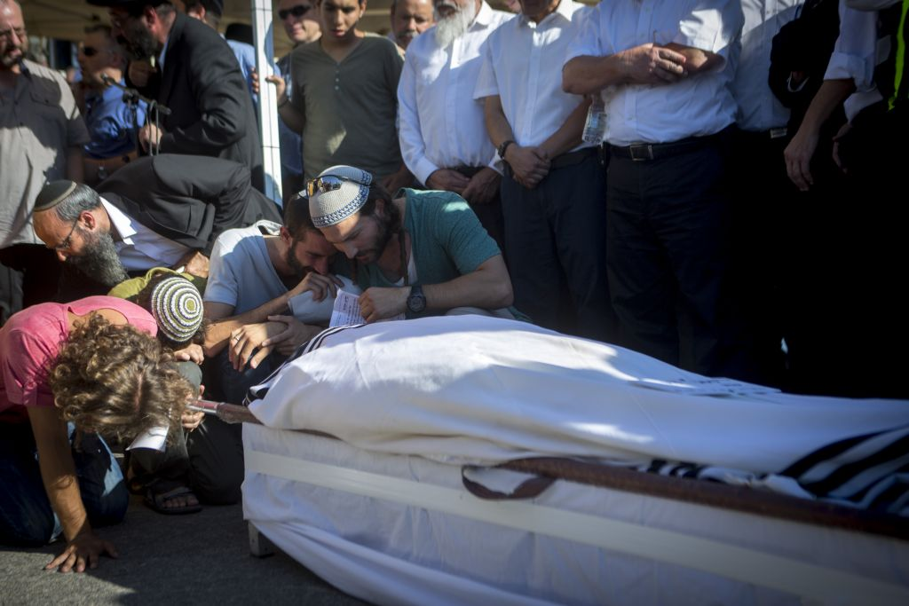 The family of Rabbi Miki Mark mourn at his funeral at Har Hamenuchot cemetery in Jerusalem on July 3, 2016. Mark was murdered in a terror attack on Friday, when his family's car came under gunfire from a passing vehicle and overturned near Beit Hagai on Route 60 in the West Bank. (Miriam Alster/Flash90)