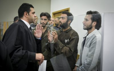 Khalid Muhamra, left, Younis Ayash Musa Zayn, center, and Muhammad Muhamra, right, speak with an attorney during their indictment in a Tel Aviv District Court on July 4, 2016. The three Palestinian men have been charged with murder in connection with the terror attack at the Sarona Market in central Tel Aviv in which four Israelis were killed. (Flash90)