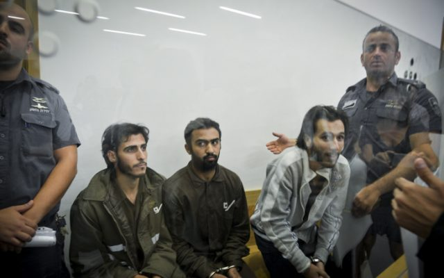 Khalid Muhamra, left, Younis Ayash Musa Zayn, center, and Muhammad Muhamra, right, sit behind a glass window during their indictment in a Tel Aviv District Court on July 4, 2016. (Flash90)