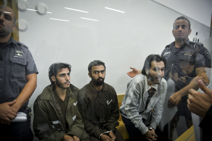Khalid Muhamra, left, Younis Ayash Musa Zayn, center, and Muhammad Muhamra, right, sit behind a glass window during their indictment in a Tel Aviv District Court on July 4, 2016. The three Palestinian men have been charged with murder in connection with the terror attack at the Sarona Market in central Tel Aviv in which four Israelis were killed. (Flash90)