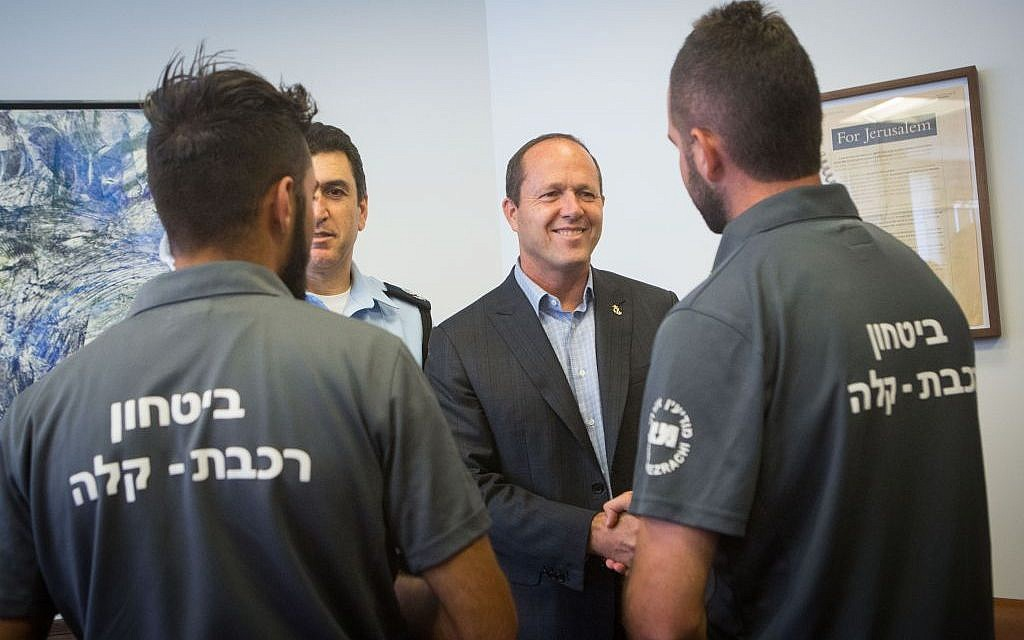 Jerusalem District Police Commander, Yoram Halevi, second left, and Jerusalem mayor Nir Barkat, second right, meet and congratulate light rail security guards who prevented a bombing on July 17, 2016. (Miriam Alster/Flash90)