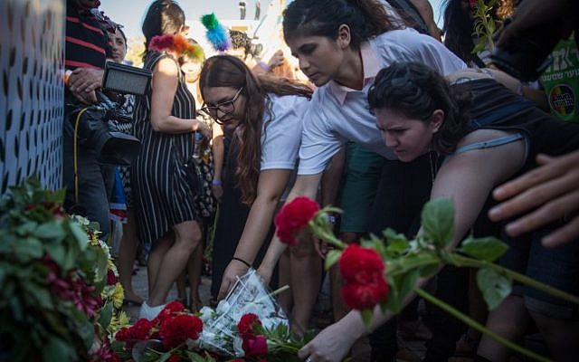 Participants lay flowers at the site where Shira Banki was stabbed to death at last year's Pride Parade, during the annual parade in Jerusalem attended by more than 25,000, on July 21, 2016. (Hadas Parush/Flash90)
