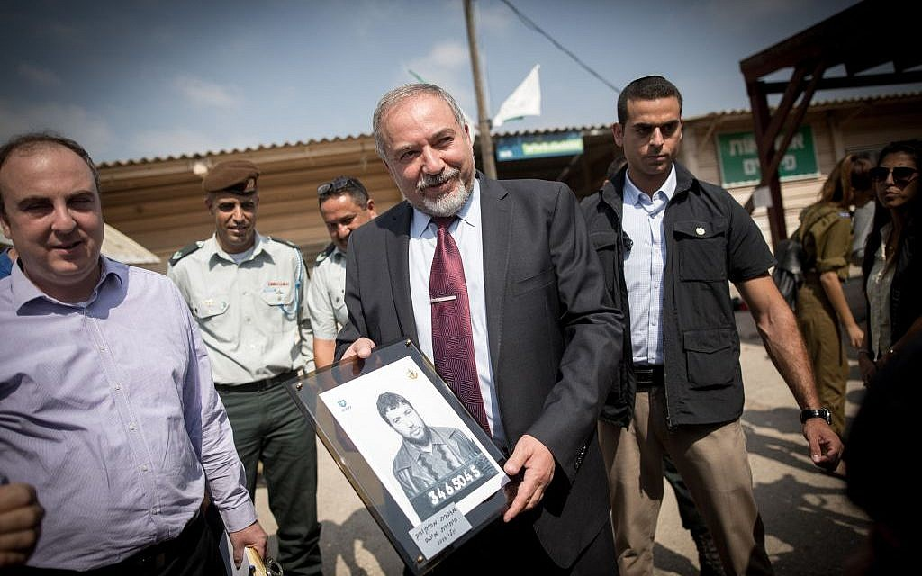 Defense Minister Avigdor Liberman holds up a picture of himself as a new army recruit at an IDF induction ceremony at the Tel Hashomer army base outside Tel Aviv on July 25, 2016. (Miriam Alster/Flash90)