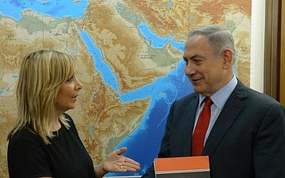 Prime Minister Benjamin Netanyahu, right, receives the report of the Palmor Committee to eradicate racism against Ethiopian Israelis, from the hands of Justice Ministry Director General Emi Palmor at the Prime Minister's Office in Jerusalem, July 31, 2016. (Amos Ben Gershom/GPO)