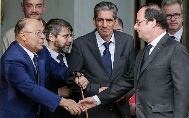 French President Francois Hollande shakes hands with Paris Mosque rector Dalil Boubakeur, left, after a meeting with religious representatives at the Elysee Palace in Paris, following yesterday attack at a church in Normandy, Wednesday, July 27, 2016. (AP Photo/Thomas Padilla)