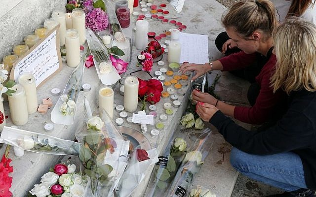 Flowers, candles and messages are placed on the city hall entrance closed to the home of Father Jacques Hamel after he was killed during an attack in a church in Saint-Etienne-du-Rouvray, Normandy, France, Tuesday, July 26, 2016. (AP Photo/Francois Mori)