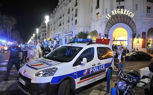 A police car is parked near the scene of an attack after a truck drove on to the sidewalk and plowed through a crowd of revelers who'd gathered to watch the fireworks in the French resort city of Nice, southern France, Friday, July 15, 2016(AP Photo/Christian Alminana)