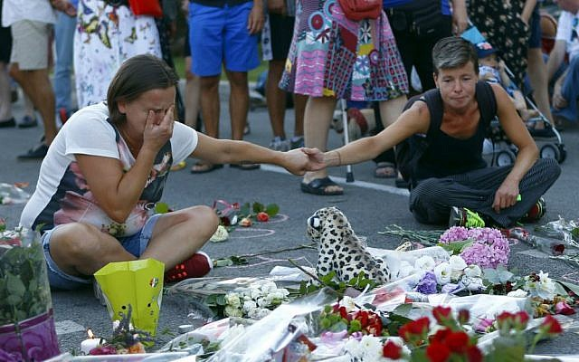 People pay tribute to the victims at the site of a deadly truck attack on the famed Promenade des Anglais in Nice, southern France, Saturday, July 16, 2016. (AP Photo/Francois Mori)