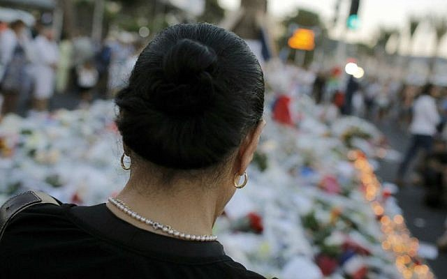 A woman pays tribute to the victims of a deadly terror attack at the site on the famed Boulevard des Anglais in Nice, southern France, Saturday, July 16, 2016. (AP Photo/Laurent Cipriani)