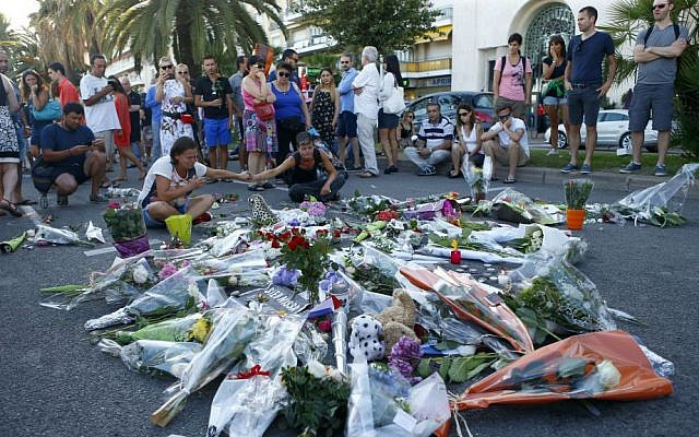 People pay tribute to the victims at the site of a deadly terror attack on the famed Promenade des Anglais in Nice, southern France, Saturday, July 16, 2016. (AP Photo/Francois Mori)