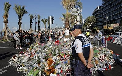 A police officer watches people gathering around a floral tribute for the victims killed during a deadly attack in Nice, southern France, Sunday, July 17, 2016. (AP/Laurent Cipriani)