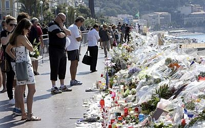 People look at flowers and messages placed along the beach of the Promenade des Anglais in Nice, southern France, Tuesday, July 19, 2016, where dozens were killed in last week's Bastille Day truck attack. (AP Photo/Claude Paris)