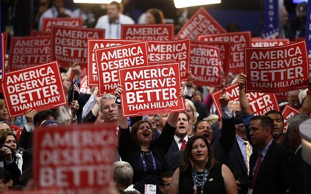 Delegates hold signs as Gov. Scott Walker of Wisconsin speaks during the third day of the Republican National Convention in Cleveland, Wednesday, July 20, 2016. (AP Photo/Paul Sancya)