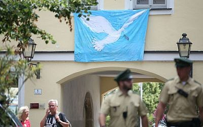 Police officers walk past a wall with a peace dove on a banner at the site of the attack in Ansbach, Germany, Tuesday, July 26, 2016. (Daniel Karmann/dpa via AP)
