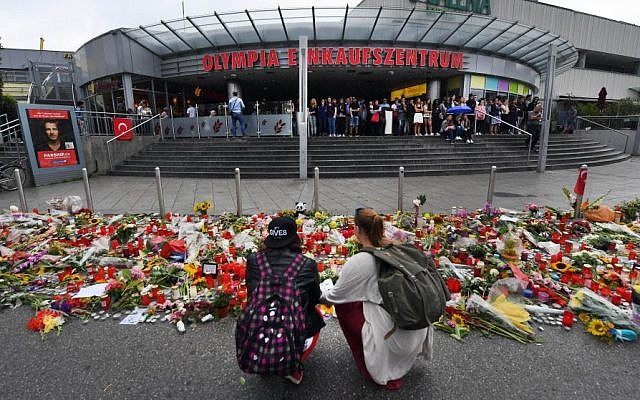 Flowers and candles have been placed in front of the main entrance of the Olympia-Einkaufszentrum shopping mall in Munich, Germany, Monday, July 25, 2016, after a rampage that left numerous people dead and injured. (Peter Kneffel/dpa via AP).