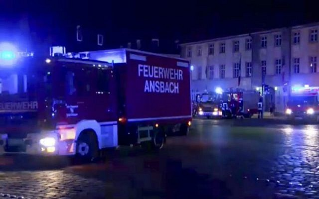 In this image taken from video, fire trucks and ambulances stand in the city center of Ansbach near Nuremberg, southern Germany, Monday morning, July 25, 2016, after a man was killed when an explosive device he was believed to be carrying went off near an open-air music festival, injuring 12 others. (News5 via AP)