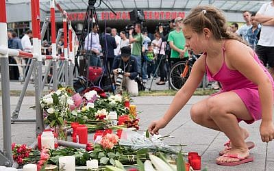 A girl puts down flowers in front of the Olympia shopping center were a shooting took place, leaving nine people dead the day before on Saturday, July 23, 2016 in Munich, Germany. (AP Photo/Sebastian Widmann)