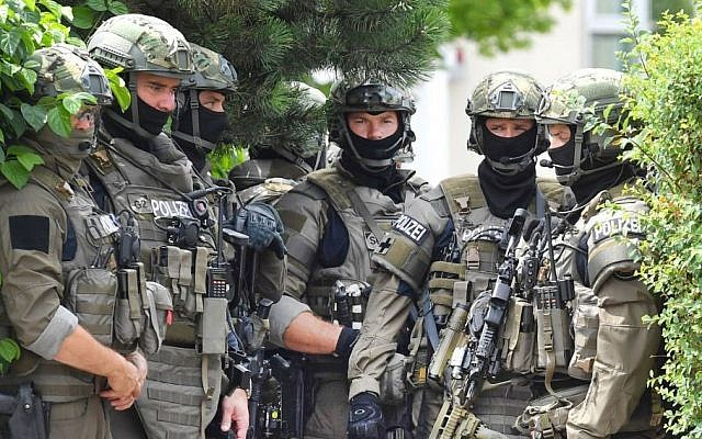 Members of a special forces stand near a fast food restaurant where a shooting took place leaving nine people dead the day before on Saturday, July 23, 2016 in Munich, Germany. (AP/Kerstin Joensson)