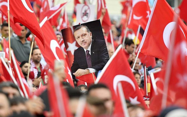 A picture of Turkish president Erdogan is framed by national flags during a demonstration in Cologne, Germany, Sunday, July 31, 2016. (AP Photo/Martin Meissner)