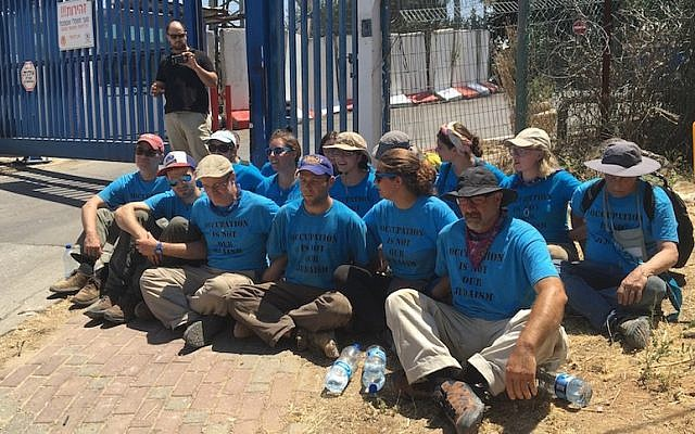 Ethan Buckner, second from left in front, and other activists from the Center for Jewish Nonviolence protesting outside the jail in the West Bank Jewish settlement Kiryat Arba, July 16, 2016. (Andrew Tobin)