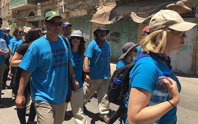 Illustrative: Peter Beinart, left, marching with other activists from the Center for Jewish Nonviolence through the West Bank city of Hebron, July 16, 2016. On the right is the movement's CEO, Ilana Sumka. (Andrew Tobin)