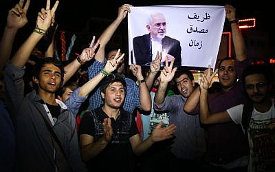 FILE -- In this July 14, 2015 file photo, young Iranian men cheer and show victory signs while holding a picture of Foreign Minister Mohammad Javad Zarif. (AP Photo/Ebrahim Noroozi, File)