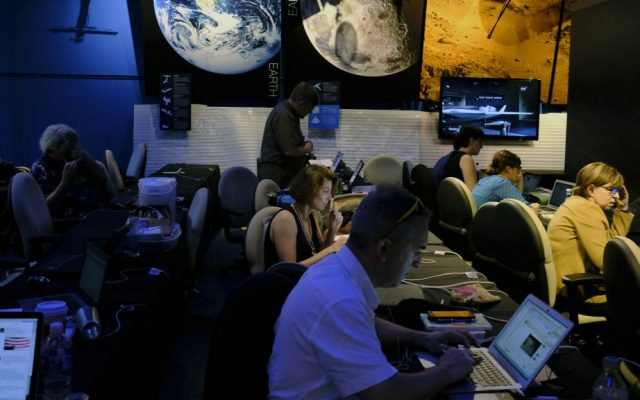 Journalists work in preparation for NASA's Juno spacecraft's orbit around Jupiter in the media center at Jet Propulsion Laboratory, in Pasadena, California, Monday, July 4, 2016. (AP Photo/Richard Vogel)