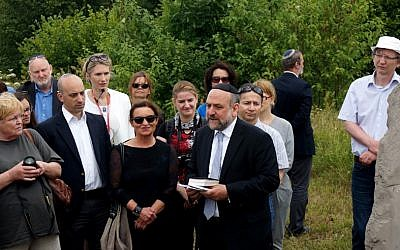 Michael Schudrich, Poland's chief rabbi, reciting a prayer for the victims of the Jedwabne massacre at the town's Jewish cemetery, July 10, 2016. Jonathan Greenblatt, CEO and national director of the Anti-Defamation League, is front row, second from left. (JTA/Cnaan Liphshiz)