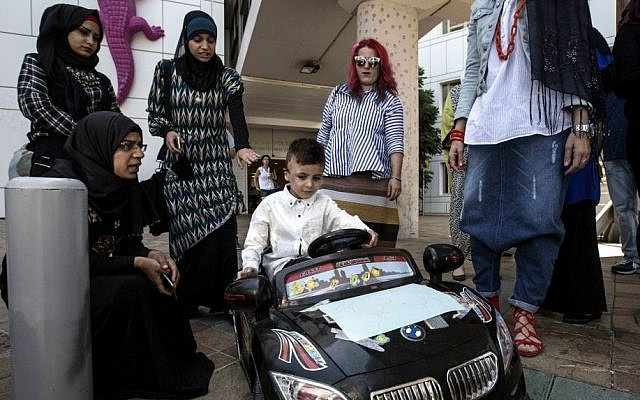 Palestinian relatives gather around Ahmad Dawabsha, the sole survivor of a West Bank arson attack in Duma village, as he rides a toy car at the Tel HaShomer Hospital in the city of Ramat Gan, Israel, Friday, July 22, 2016.(AP Photo/Tsafrir Abayov)