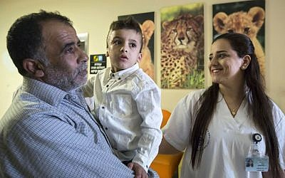 Ahmed Dawabsha, the sole survivor of a West Bank arson attack in Duma village, is carried by his grandfather Hussein at the Tel HaShomer Hospital in Ramat Gan, Israel on Friday, July 22, 2016 (AP Photo/Tsafrir Abayov)