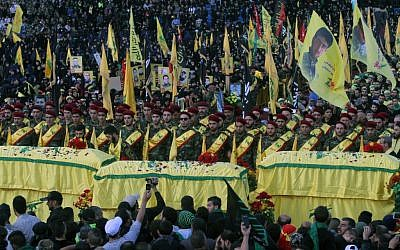 In this Tuesday, Oct. 27, 2015 file photo, relatives and comrades pray as they surround the Hezbollah flag-draped coffins of Shiite fighters who were killed in Syria, during a rally to mark the 13th day of the Shiite mourning period of Muharram, in Nabatiyeh, Lebanon. (AP Photo/Mohammed Zaatari, File)