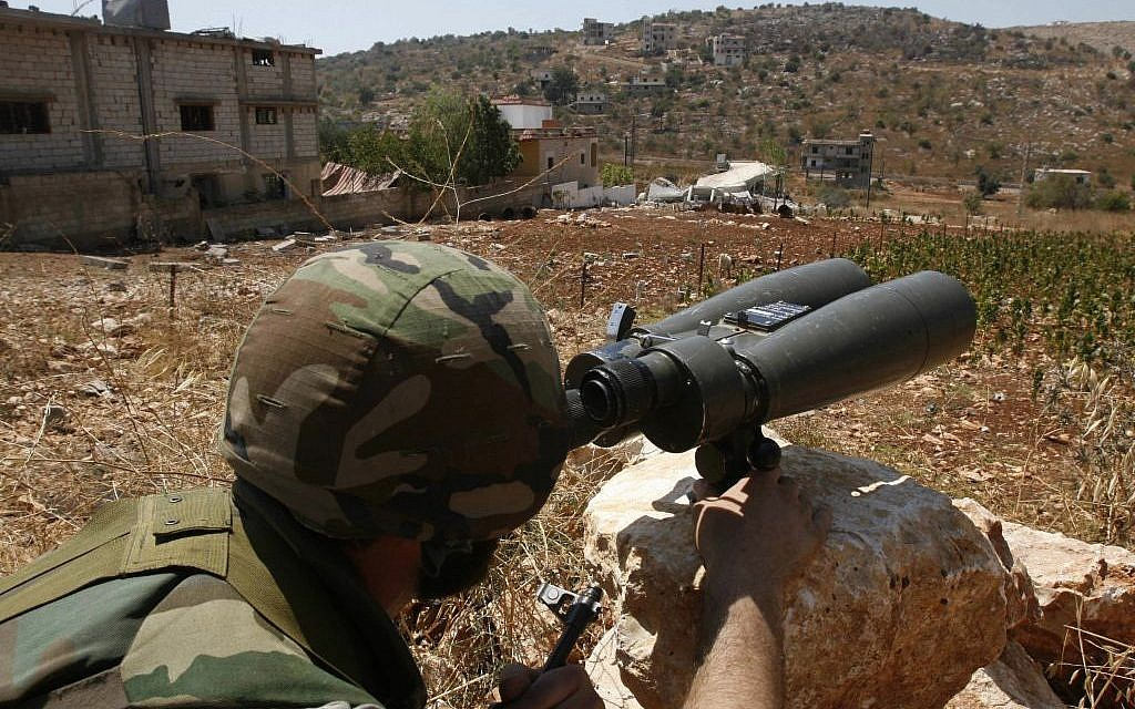In this Wednesday, Aug. 16, 2006 file photo, a Hezbollah fighter, who refused to be identified, uses binoculars to scan for Israeli forces' positions, in the outskirts of the southern village of Aitaroun, close to the town of Bint Jbeil. (AP Photo / Mohammed Zaatari, File)
