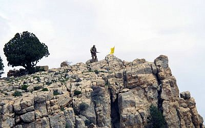 In this Saturday, May 9, 2015 photo, a Hezbollah fighter stands on a hill next to the group's yellow flag in the fields of the Syrian town of Assal al-Ward in the mountainous region of Qalamoun, Syria.  (AP Photo/Bassem Mroue, File)