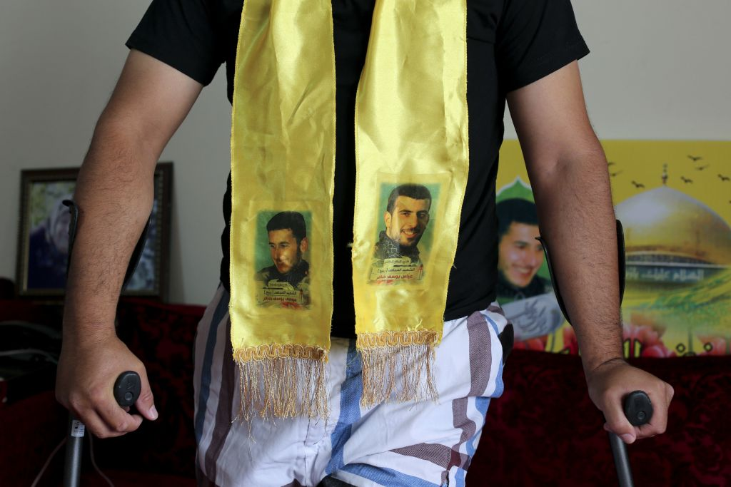 Hezbollah member Hisham Khanafer uses crutches as he arrives for an interview with The Associated Press wearing a scarf with the pictures of his brothers Moussa, left, who was killed on July 24, 2006 and Abbas, who was killed on May 15, 2015 in Syria. June 29, 2016 (AP Photo/Hassan Ammar)