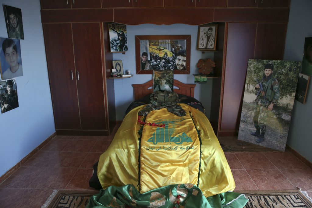In this Wednesday, June 29, 2016, photo a Hezbollah flag covers the bed of slain Hezbollah fighter Khalil Ibrahim, portrayed, who was killed in a Damascus suburb known as Ghouta, on Dec. 27, 2013, in the southern village of Aynata, close to the town of Bint Jbail, Lebanon. (AP Photo/Hassan Ammar)