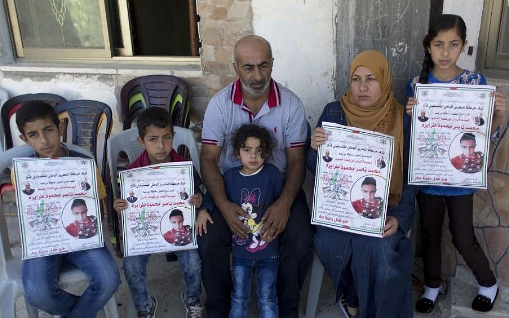 Nasser Tarayrah, center, and his wife Raeda, second right, parents of Palestinian terrorist Muhammad Tarayrah, who murdered Hallel Ariel on June 30, 2016 as she slept in her home in Kiryat Arba, pose for a picture with some of their children, in the West Bank village of Bani Na'im, near Hebron, July 9, 2016 (AP Photo/Nasser Nasser)