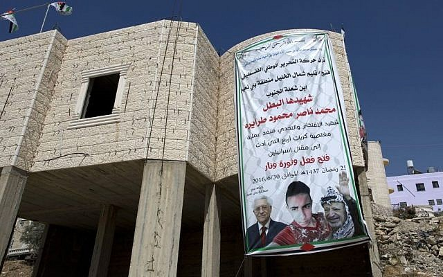 A banner with pictures of the late Palestinian leader Yasser Arafat, President Mahmoud Abbas and killer Mohammed Tarayrah, July 9, 2016 (AP Photo/Nasser Nasser)