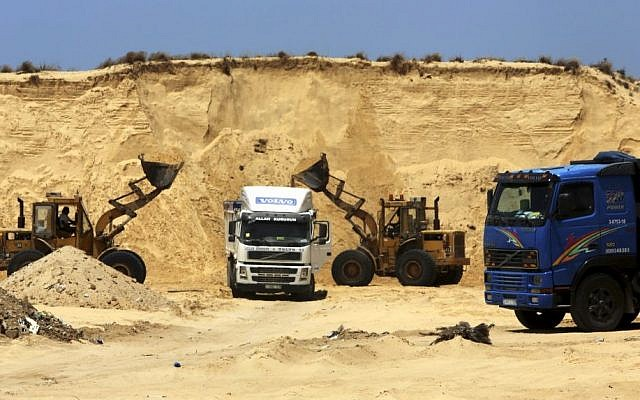 Palestinian diggers dump sand into a truck at the site of Al-Isra 2 housing project in Khan Younis, Gaza Strip, July 20, 2016 (AP Photo/Adel Hana)